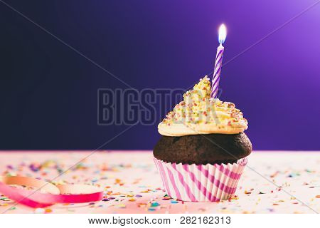 Birthday Cupcake With Single Candle On Pink And Purple Background.