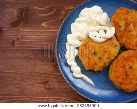 Rissoles Of Ham, Cheese  And Potatoes With Sour Cream On Blue Plate On Rustic Wooden Background Flat