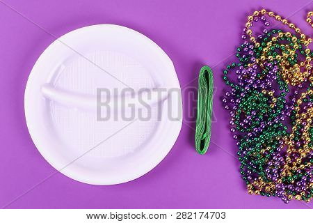 DIY wreath Mardi Gras, Fat Tuesday purple background. Gift idea, decor Mardi Gras. Wreath plastic plates, satin ribbon, green, yellow, purple bead. Step by step. Process children craft. Top view. poster