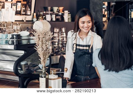 Asian Woman Barista Wear Jean Apron Holding Coffee Cup Served To Customer At Bar Counter With Smile