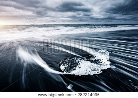 Incredible piece of the iceberg sparkle on black sand. Location Jokulsarlon lagoon, Diamond beach, Vatnajokull national park, Iceland, Europe. Long exposure photography. Discover the beauty of earth.