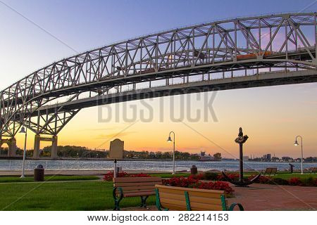 Blue Water Bridge Sunrise. Dawn Over The Towns Of Port Huron, Michigan And Sarnia, Ontario On The Us