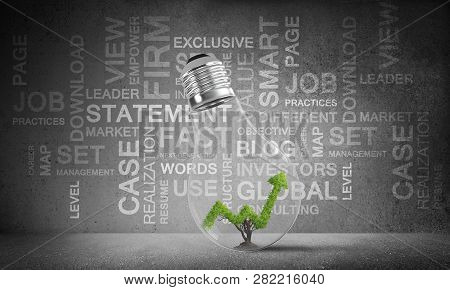 Lightbulb With Growing Green Arrow Graph Inside Placed Against Business Related Terms On Grey Wall O