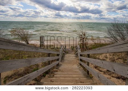 Wooden Stairs To Beach. Long Wooden Staircase Leads To A Sunny Sandy Beach On The Michigan Coast Of