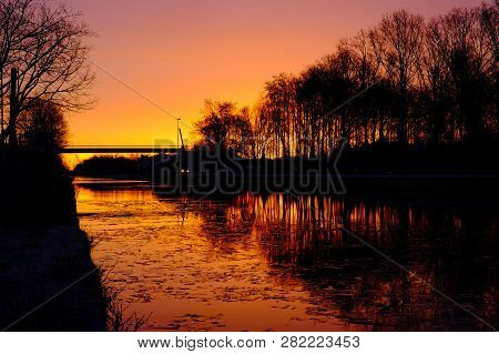 Dramatic And Colorful Sunrise Over A Beautiful Early Winter Landscape With A Frozen River Or Canal,