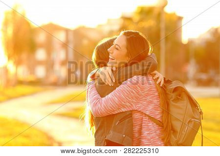 Two Happy Friends Meeting And Hugging In A Park At Sunset With A Warm Light