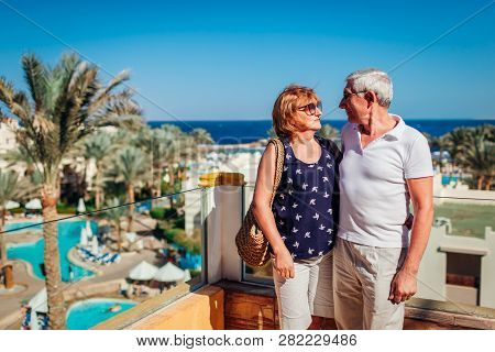 Senior Couple Walking On Hotel Territory Admiring The Sea View. People Enjoying Vacation. Traveling