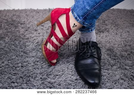 Personal Has A Lady`s Boot On One Foot, And On The Other A Male Boot.the Person Has A Third-gender T