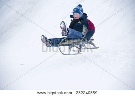 Belarus, The City Of Gomel, January 07, 2018.central Park.sledding Off A Snow Slide.the Boy Drives O