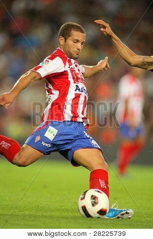 BARCELONA - SEPT 22: Alberto Lora of Gijon in action during spanish league match between FC Barcelona and Sporting Gijon at Nou Camp Stadium in Barcelona, Spain. September 22, 2010