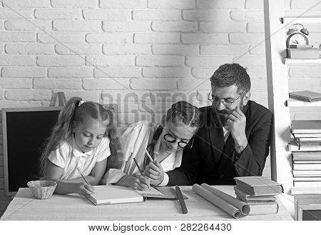 Teacher Man And Small Girls Writing At School Lesson. School Time Of Girl Sisters With Father. Back