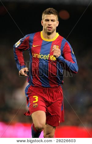 BARCELONA - FEB 20: Pique of Barcelona during the match between FC Barcelona and Athletic de Bilbao at the Nou Camp Stadium on February 20, 2011 in Barcelona, Spain