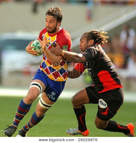 BARCELONA - APRIL 9: Perpignan's Guiry is tackled by Toulon's Gabiriele during the Heineken European Cup match USAP Perpignan against RC Toulon at the Olympic Stadium in Barcelona, on April 9, 2011
