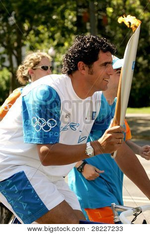 BARCELONA - JUNE 28: Spanish cyclist Miguel Indurain carries the Athens 2004 Olympic torch during the Barcelona Torch Route through the city streets on June 28, 2004 in Barcelona, Spain