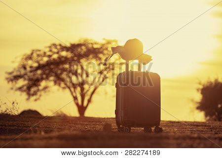 Suitcase And Hat With Background Sunset.