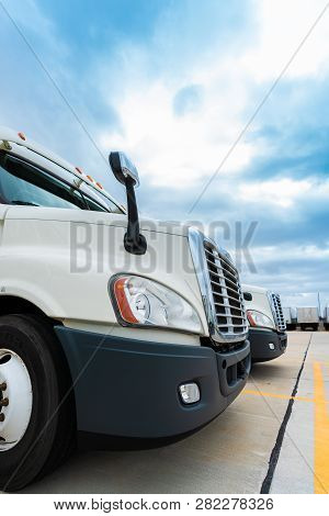 Fleet Of White 18 Wheeler Semi Trucks Ready To Deliver Freight
