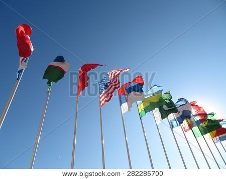 National Flags Waving On Blue Sky Background. Concept Of  International Relations, Summit