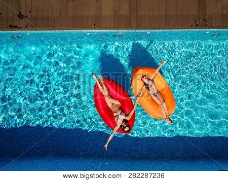 Two Girls Are Swimming In The Pool