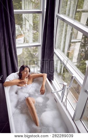 young woman in bath drink champagne and relaxing top view