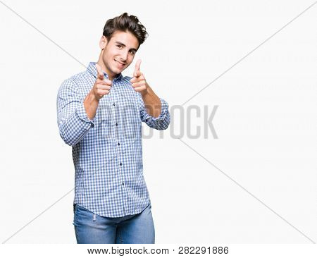 Young handsome business man over isolated background pointing fingers to camera with happy and funny face. Good energy and vibes.