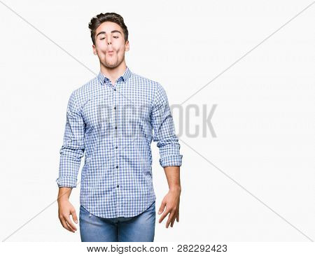 Young handsome business man over isolated background making fish face with lips, crazy and comical gesture. Funny expression.