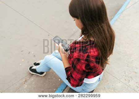 Girl Teenager 11-12 Years Old Sits On Skateboard In Park Summer Against Background Concrete Stairs.