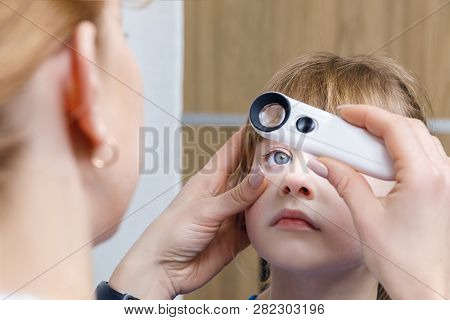 A Closeup Of Female Ophthalmologist Checking Eye Of Small Child Or Performing The Post Treatment Exa