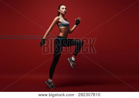 Full Of Energy. Sportswoman Jumping With Resistance Band Over Red Background, Isolated