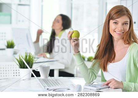 Two Businesswomen Working At Modern Office During Lunch Time