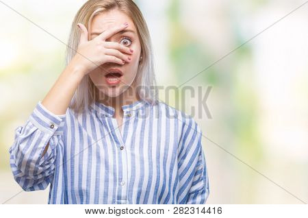 Young blonde woman over isolated background peeking in shock covering face and eyes with hand, looking through fingers with embarrassed expression.