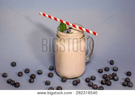 Blueberry smoothie with mint leaf and straw on blue backround