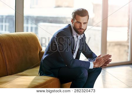Confident And Concentrated. Thoughtful Handsome Businessman Is Thinking While Sitting In His Modern