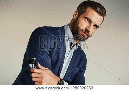 Portrait Of A Sexy Handsome And Bearded Businessman In Elegant Suit Standing At Office.