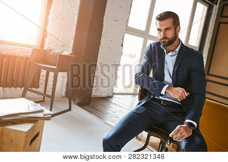 Always Perfect...charming And Pleasant And Bearded Businessman In Stylish Suit Sitting In Armchair A