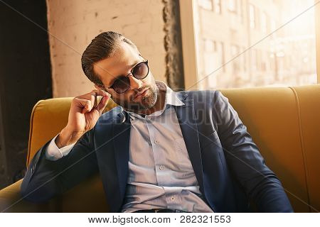 Sexy Bearded Businessman In Sunglasses Dressed In Very Fashionable And Stylish Suit Is Sitting At Of
