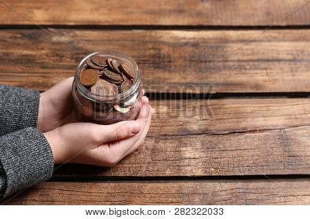 Woman Holding Donation Jar With Coins At Wooden Table, Closeup. Space For Text