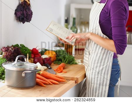 Young Woman Reading Cookbook In The Kitchen, Looking For Recipe . Young Woman