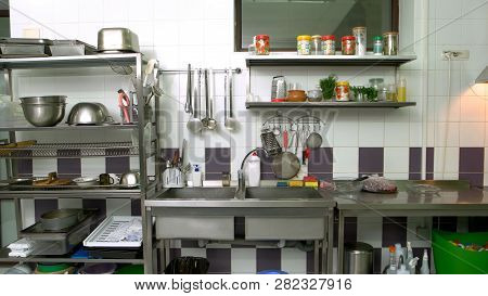 Various Utensils At Commercial Kitchen. Cooking Utensils On Counter In Commercial Kitchen. Cooking E