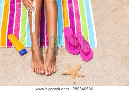 Sunscreen woman applying sun tan cream sunblock lotion on legs with bottle, flip flops and sea star on colorful beach towel on sand. Suntan protection on beach summer travel vacation. female model.
