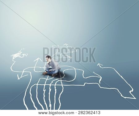 Confused Man Sitting On Different Arrows Drawn On The Ground . The Concept Of Hard Choices.