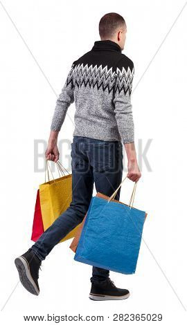 Side view of going man with shopping bags. guy in motion. backside view of person. Rear view people collection. Isolated over white background. A guy in a warm sweater walks by with lots of shopping.