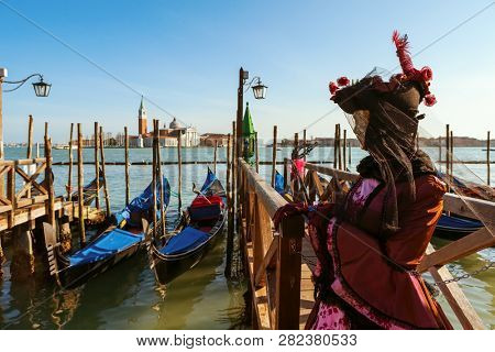 VENICE, ITALY - MARCH 04, 2011:  Woman dressed in costume stands near gondolas on Grand Canal as San Giorgio Maggiore on background during traditional famous Carnival taking place in Venice, Italy.
