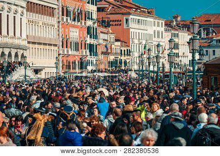 VENICE, ITALY - FEBRUARY 18, 2017: Crowds of tourists walking by typical venetian buildings near San Marco Square during famous  traditional carnival taking place each year in Venice, Italy.