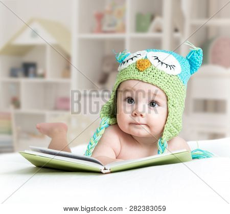 Baby In Funny Owl Knitted Hat Owl Lying With Book In Nursery