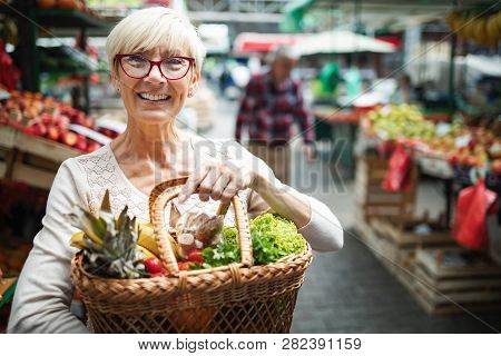 Senior Woman Buying Vegetables At The Green Market.