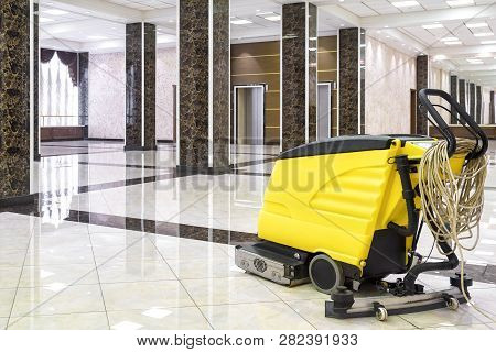 Cleaning Machine In The Empty Office Lobby. Yellow Vacuum Equipment For Cleaning Is On The Shiny Mar