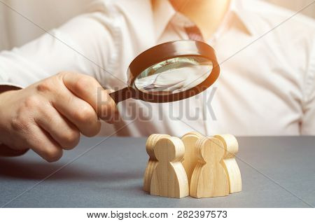 Business Leader Holding A Magnifying Glass Over A Team Of Workers. The Concept Of Finding New Employ