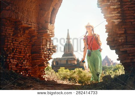 Positive Emotions. Happy Woman Traveler With A Backpack Walking Through The Old Bagan Looking The An