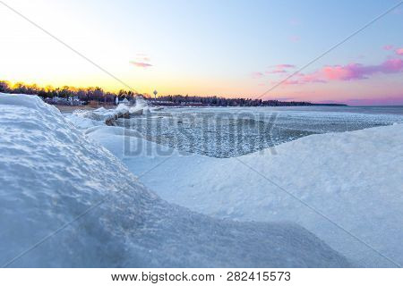 Frozen Lake Sunrise. Sunrise Over A Huge Snow Bank And Waves On The Shores Of Lake Huron In Michigan