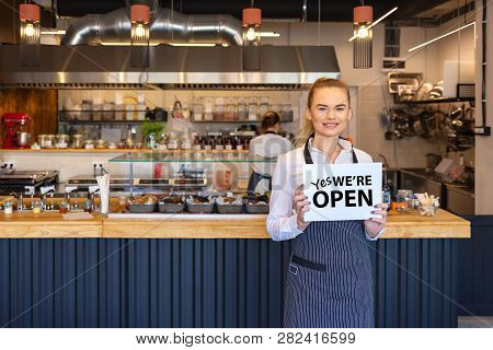 Portrait Of Smiling Owner Standing In His Restaurant With Open Signboard. Young Entrepreneur Woman A